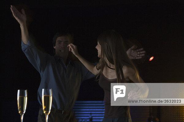 Paare tanzen im Nachtclub  Gläser Champagner im Vordergrund