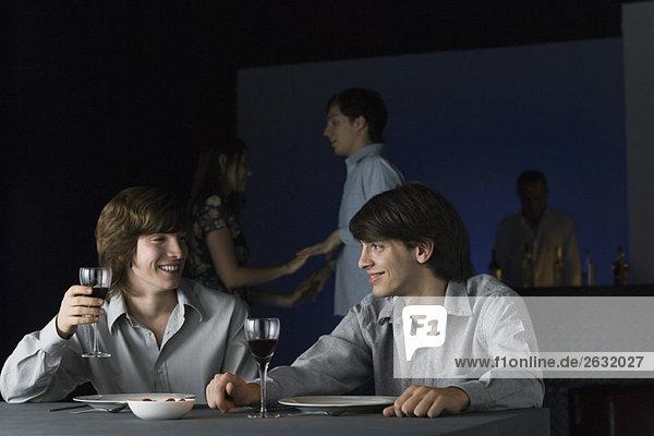 Freunde  die zusammen im Nachtclub Wein trinken  sich gegenseitig anlächeln  Pärchen  die im Hintergrund tanzen