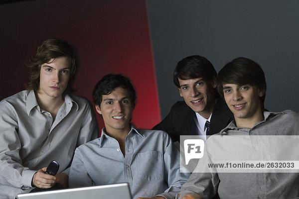 Professionelle Männer sitzen Seite an Seite  lächeln in die Kamera  Porträt