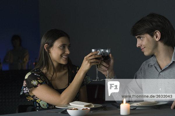 Ein paar klirrende Gläser im Restaurant  die sich gegenseitig anlächeln.
