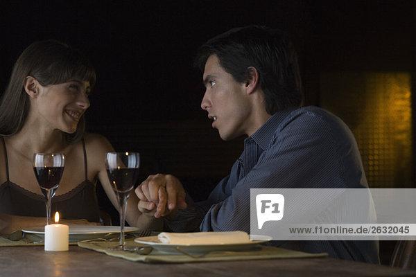 Paar hält sich beim romantischen Abendessen an den Händen und schaut sich an.