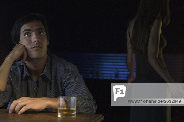 Mann sitzt neben einem Glas Whiskey  schaut auf  Frau tanzt im Hintergrund
