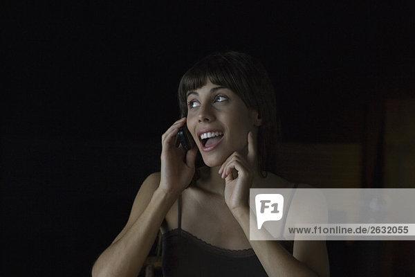 Frau spricht fröhlich am Handy  schaut weg  gestikuliert