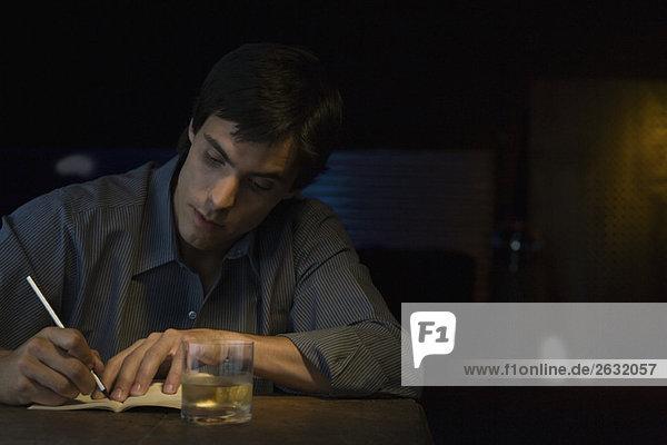 Mann schreibt in Notizbuch  sitzt in der Bar.