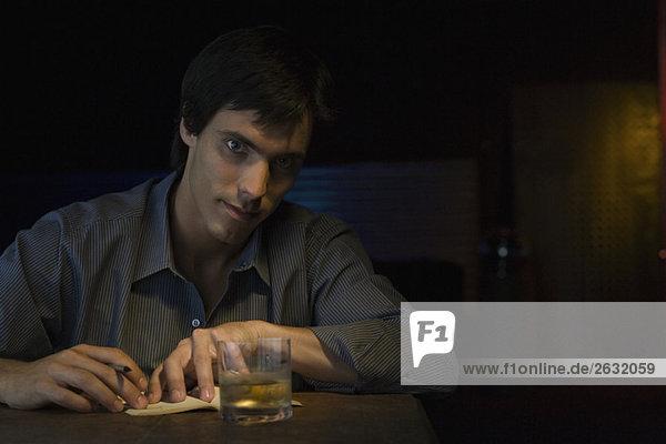 Mann sitzt in der Bar mit Kugelschreiber  Notizbuch und Whiskyglas und schaut in die Kamera.