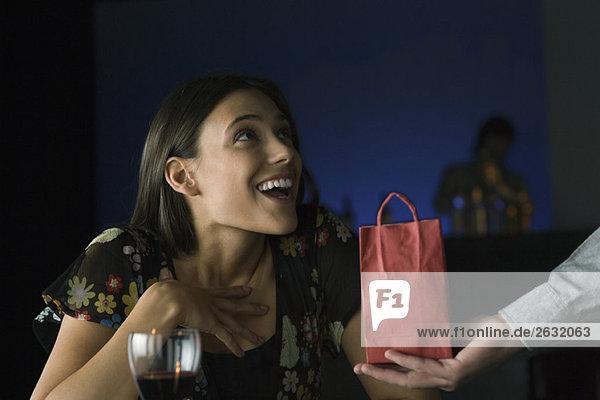 Die Frau  die mit einem Geschenk überreicht wird  schaut erstaunt auf den Geber.