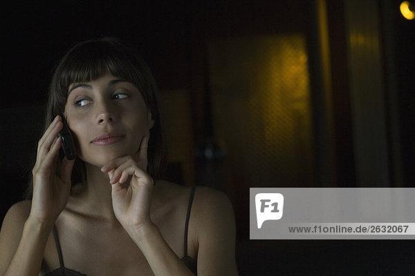 Frau spricht auf dem Handy  Hand unter dem Kinn  schaut weg.