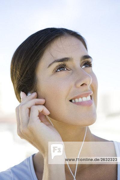 Woman looking up  listening to earphones