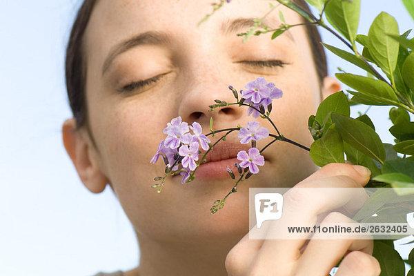 Young Woman smelling kleine lila Blüten auf Baum Young Woman smelling kleine lila Blüten auf Baum