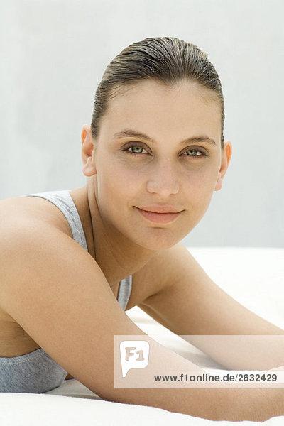 Portrait einer jungen Frau Leaning auf Ellbogen auf Futon  liegend
