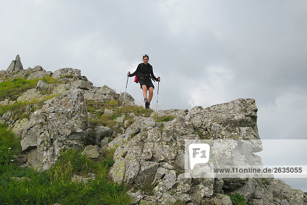 Woman backpacking along with hiking sticks