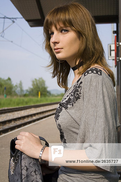 Junge Frau an einer Haltestelle
