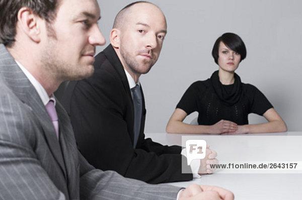 junge Frau mit zwei Geschäftsleute am Konferenztisch sitzen