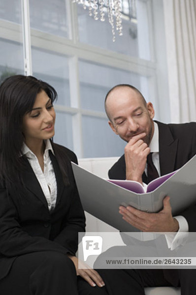 businesswoman and male colleague sitting together reading document