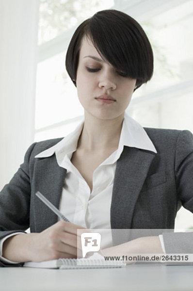 Porträt der jungen Geschäftsfrau sitzt am Schreibtisch Aufzeichnen von Notizen
