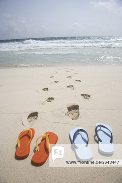two pairs of flip flops and footsteps on sandy beach