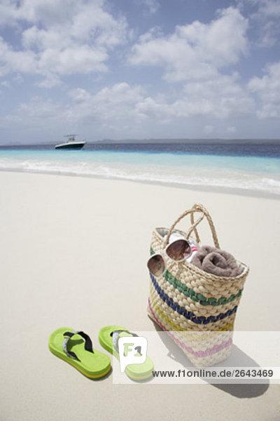 paar Flip Flops und Tasche auf sandigen Strand