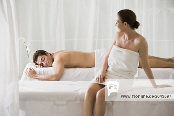 woman sitting on massage bench with man lying in background