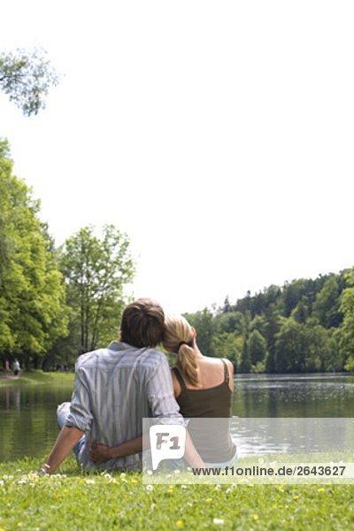 Rückansicht des jungen Paares sitzen im Park See
