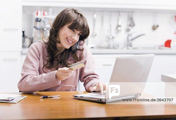 Teenagerin sitzen in Küche an Computer mit Kreditkarte