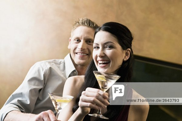 portrait of young couple in bar with cocktail glasses
