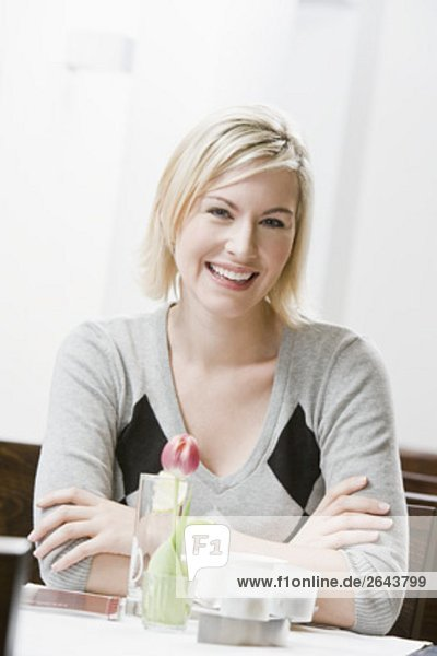 portrait of young woman sitting at restaurant table