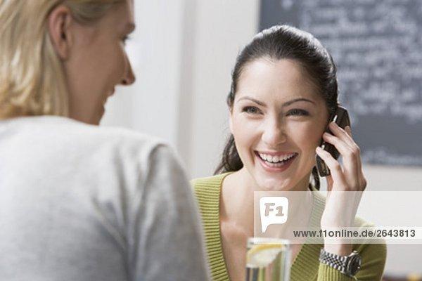 zwei Freundinnen bei Restaurant ein Gespräch auf Handy