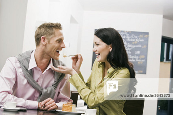 young woman feeding her boyfriend at cafe
