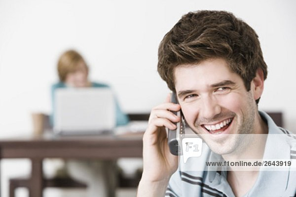 portrait of young man at home talking on the telephone