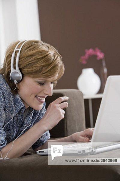 Interior  zu Hause  Frau  Computer  Notebook  arbeiten  Headset  jung  Kleidung