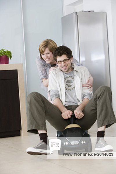 young couple having fun at home man driving toy car