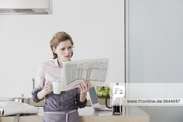 Frau am Morgen stehen in Küche Kaffee zu trinken und lesen Zeitung