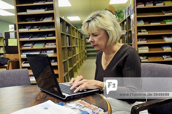 Frauen arbeiten auf einem Laptopcomputer auf eine öffentliche Bibliothek