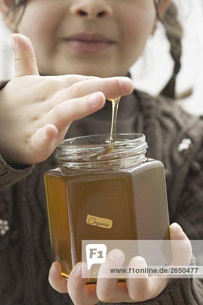 Mädchen nascht aus einem Glas Bio-Honig