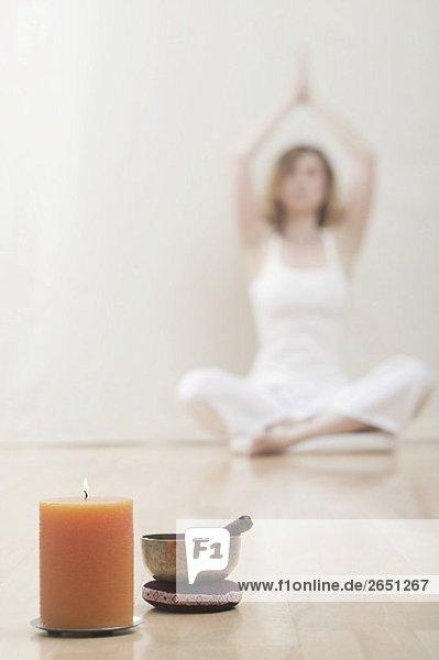 Junge Frau meditiert  eine Kerze mit Klangschale
