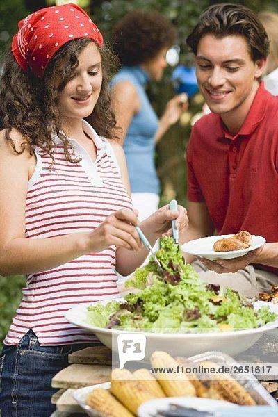 Junge Frau verteilt Blattsalat auf Teller beim Grillfest
