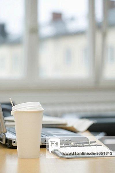 Kaffeebecher auf Schreibtisch im Büro