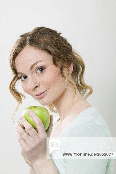 Frau hält grünen Apfel