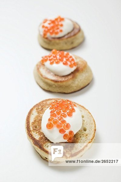 Drei Blinis mit saurer Sahne und Kaviar