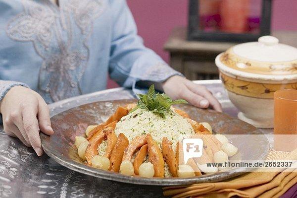 Frau serviert Couscous mit Kürbis  Minze und Zwiebeln
