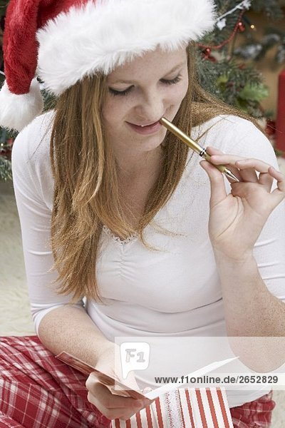 Woman in Father Christmas hat writing Christmas card