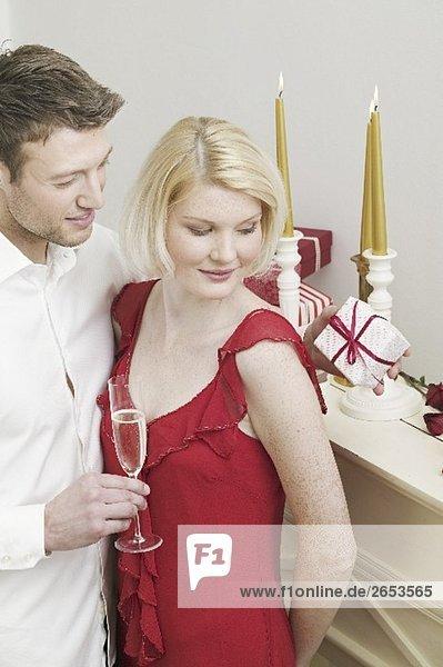 Mann überreicht Frau Weihnachtsgeschenk am Kamin