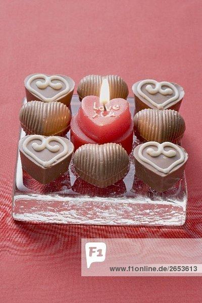 Herzförmige Kerze  umgeben von Schokoladenpralinen