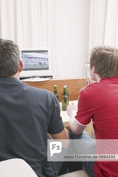 Zwei Fussballfans verfolgen Fussballspiel im Fernsehen