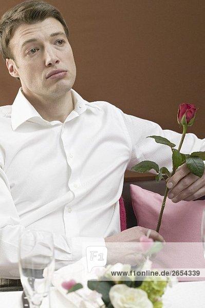 Einsamer Mann mit roter Rose im Restaurant