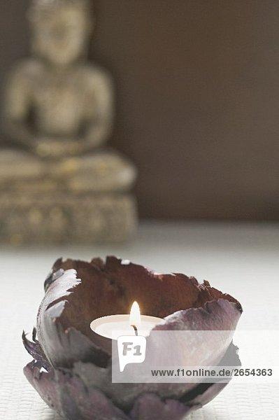 Windlicht vor Buddhastatue