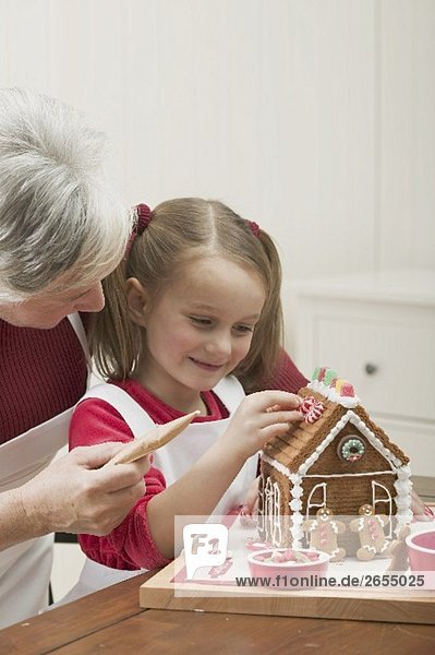 Small girl and grandmother decorating gingerbread house