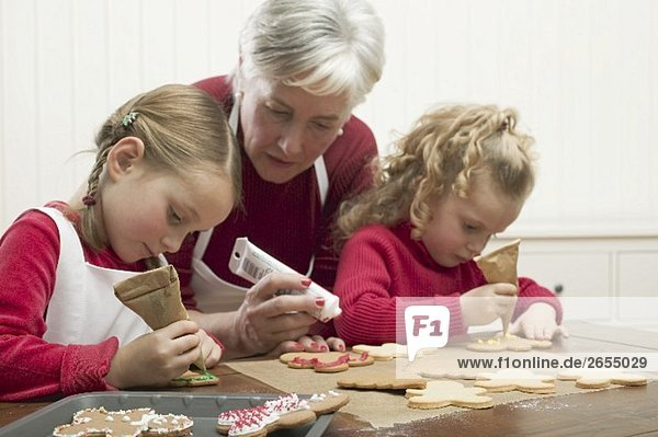 two granddaughters decorating Christmas biscuits