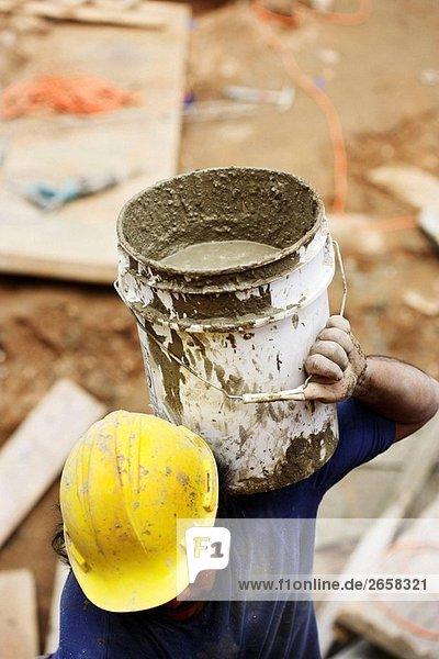 Bau/Mason Worker Durchführung Barrell gefüllt mit Zement/Beton auf Schultern