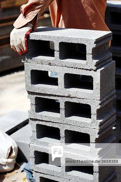 Construction Worker Hand ruht auf Haufen von Zement-Block